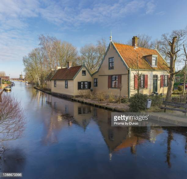 Typical wooden house and a windmill at a canal, Westzaan, Noord-Holland.