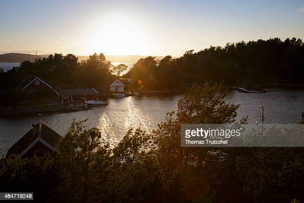 Typical wooden houses at the coast and the sea at a fjord on July 06 2015 in Kristiansand Norway