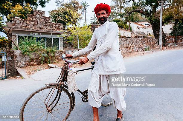 Typically dress rajasthani man walking and pushing his bicycle on the street