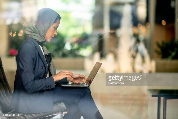 typing on a laptop - headscarf stock pictures, royalty-free photos & images