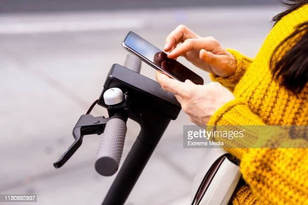 typing on a mobile phone while standing on an electric scooter - mobility scooter stock photos and pictures