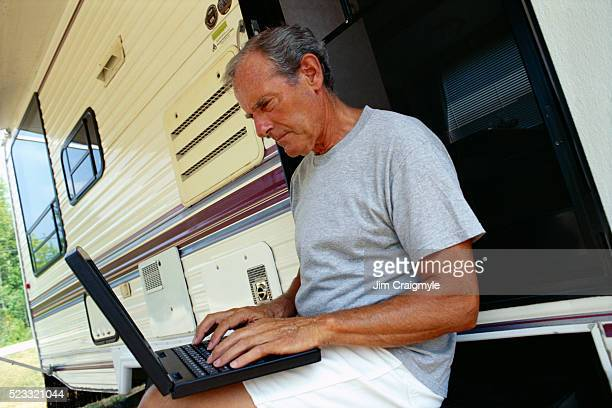 typing on laptop at motor home - jim craigmyle stock pictures, royalty-free photos & images