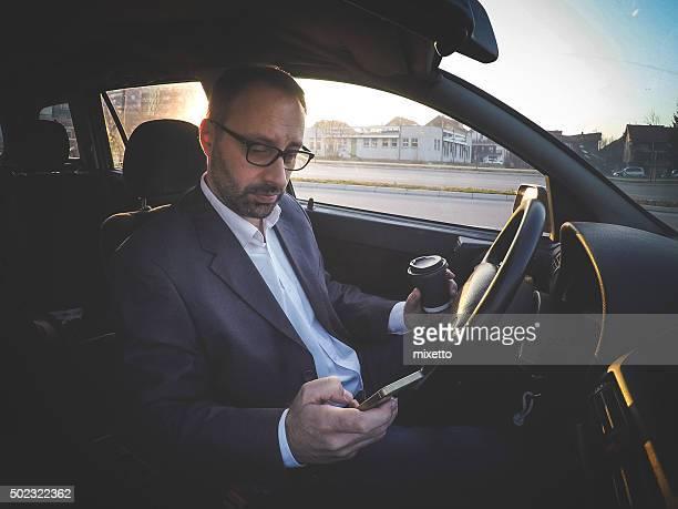タイプにスマートフォン、コーヒーを飲みながらの車
