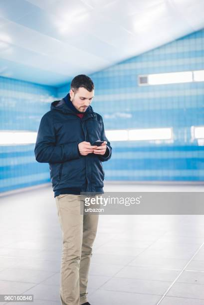 typing on smartphone - transportation building type of building stock photos and pictures