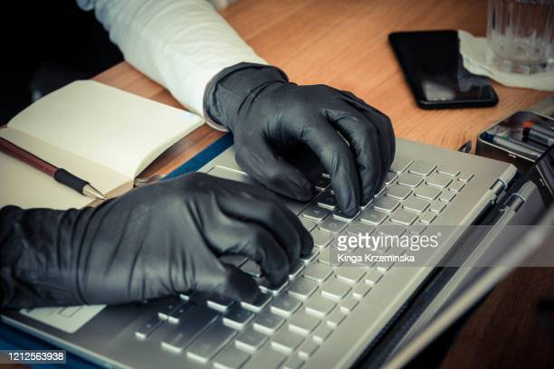 typing wearing gloves - identity theft stock pictures, royalty-free photos & images