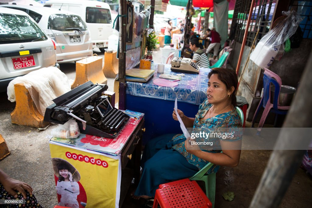 A typist sits next to a typewriter in Yangon, Myanmar, on Friday, June 16, 2017. A pariah state for decades, Myanmars recent emergence from economic isolation has attracted foreign companies and investors intrigued by the Southeast Asian nations untapped potential, abundant natural resources and low wage workforce. Photograph: Taylor Weidman/Bloomberg via Getty Images
