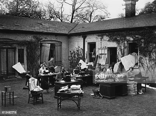 Typists at work on the lawn after St. Dunstans Headquarters in Regents Park was bombed for the third time, destroying the men's workrooms and the...