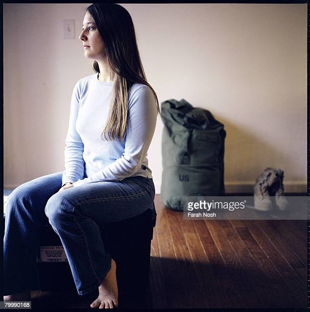Tyra Grauer sits among her husband Capt John Grauer's belongings at home on August 30 2006 in Eagle River 10 miles outside of Anchorage Alaska Over...