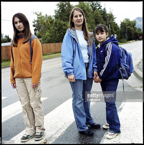 Tyra Grauer stands with her two daughters Mileah and Morriah near their home on August 30 2006 in Eagle River 10 miles outside of Anchorage Alaska...