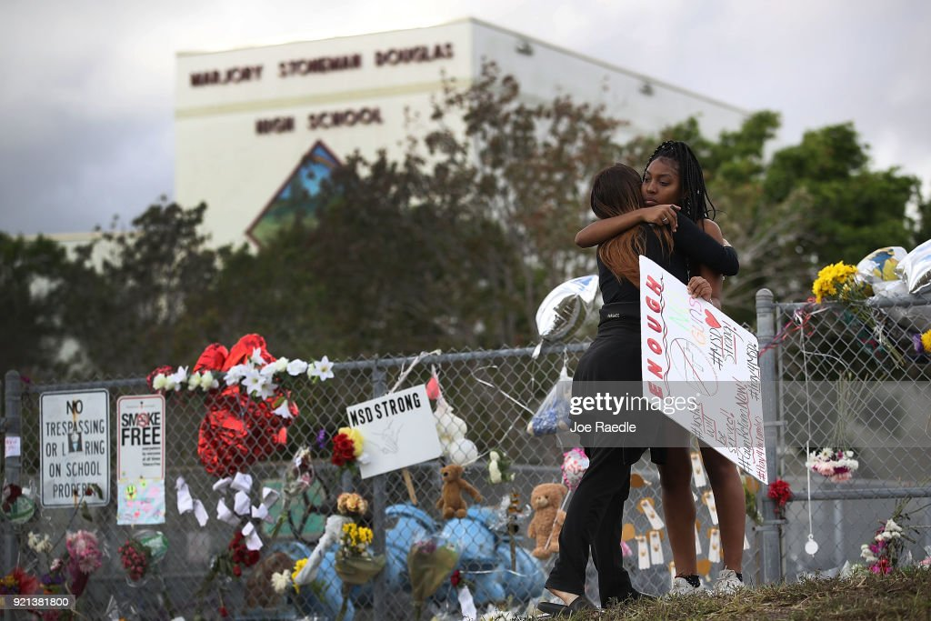 Tyra Heman (R) a senior at Marjory Stoneman Douglas High School, is hugged by Rachael Buto in front of the school where 17 people that were killed on February 14, on February 19, 2018 in Parkland, Florida. Police arrested 19-year-old former student Nikolas Cruz for killing 17 people at the high school.