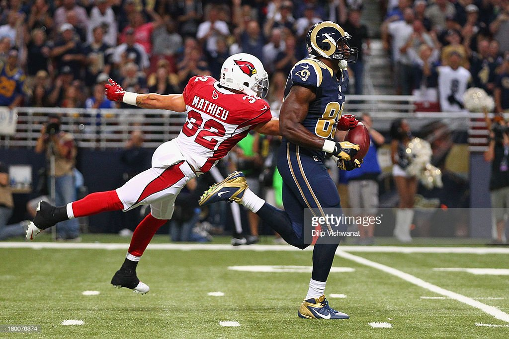 Tyrann Mathieu #32 of the Arizona Cardinals punches the ball out of the hands of Jared Cook #89 of the St. Louis Rams to prevent a touchdown at the Edward Jones Dome on September 8, 2013 in St. Louis, Missouri.