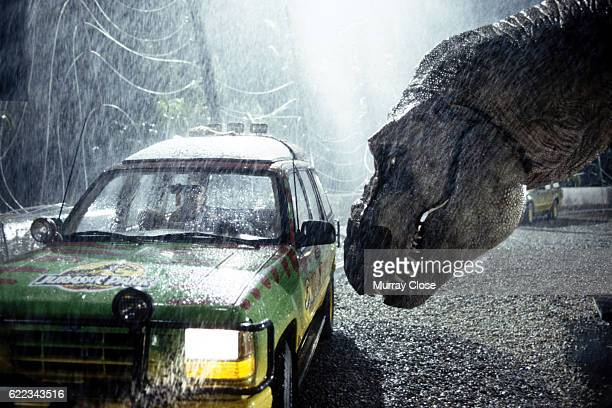 A tyrannosaurus rex terrorizes people trapped in a car in a scene from the 1993 American film Jurassic Park directed by Steven Spielberg The scifi...