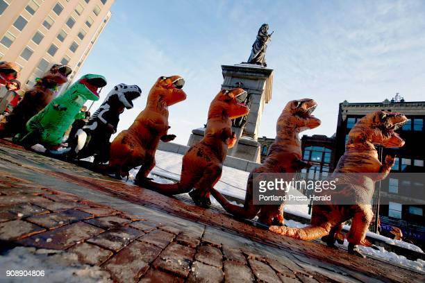Tyrannosaurus rexcostumed people march in a conga line around Our Lady of Victory on Saturday Dozens of participants and onlookers flooded Monument...