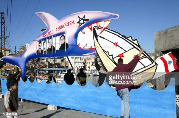 Lebanese fishermen install a giant cartoon drawing depicting Israel as a shark bearing the pictures of Lebanese prisoners jailed in Israel and a...