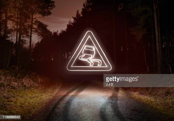 tyre skid marks and glowing slippery warning sign above forest road at night - graphic car accidents stock pictures, royalty-free photos & images