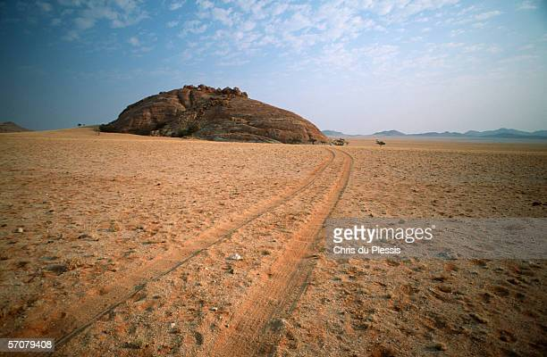 Tyre Tracks and a Rock Formation in the Desert