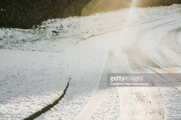 tyre tracks imprinted in snow on a winding road - falls road stock pictures, royalty-free photos & images