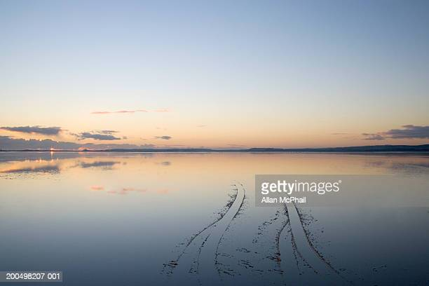 Tyre tracks in shallow water at sunset, Holy Island, Northumbria, England
