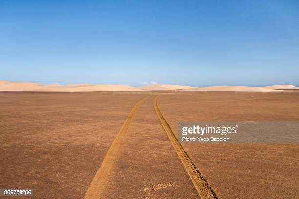 tyre tracks through the desert - thoroughfare stock photos and pictures