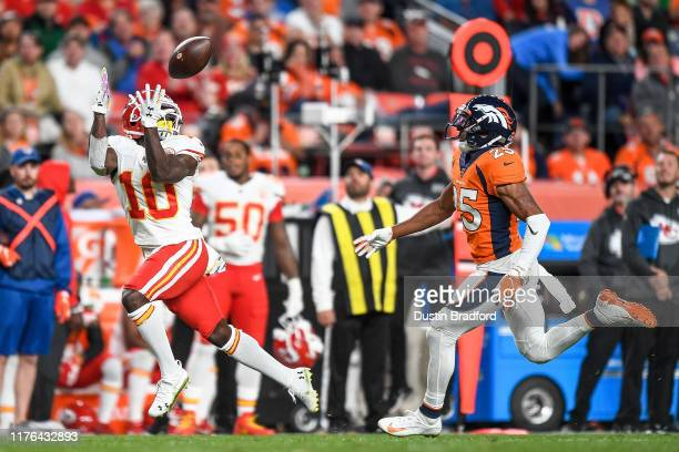 Tyreek Hill of the Kansas City Chiefs catches a pass ahead of Chris Harris of the Denver Broncos enroute to scoring a thirdquarter touchdown at...