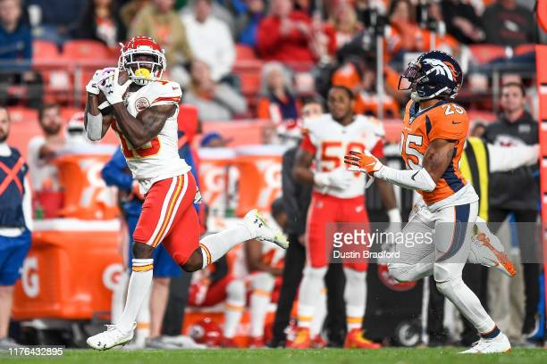 Tyreek Hill of the Kansas City Chiefs catches a pass ahead of Chris Harris of the Denver Broncos enroute to scoring a third-quarter touchdown at...