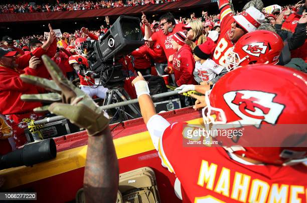 Tyreek Hill of the Kansas City Chiefs celebrates after scoring a touchdown by jumping into the stands and manning a television camera during the game...