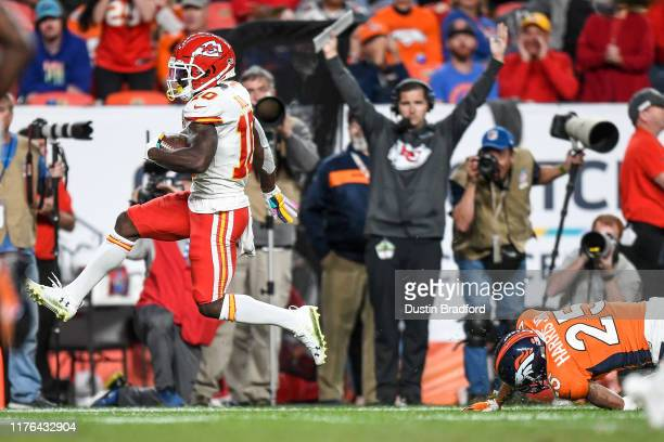 Tyreek Hill of the Kansas City Chiefs high steps a tackle attempt by Chris Harris of the Denver Broncos enroute to scoring a third-quarter touchdown...