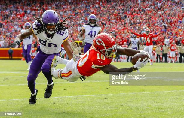 Tyreek Hill of the Kansas City Chiefs leaps to the goal line on a 40-yard touchdown pass behind the defense of Trae Waynes of the Minnesota Vikings...