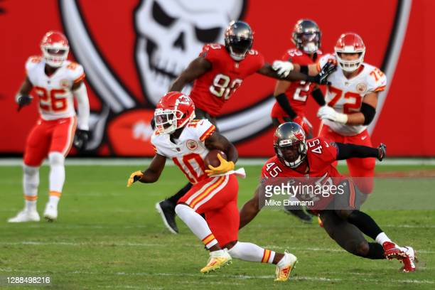 Tyreek Hill of the Kansas City Chiefs looks to gain extra yardage against Devin White of the Tampa Bay Buccaneers in the second quarter during their...