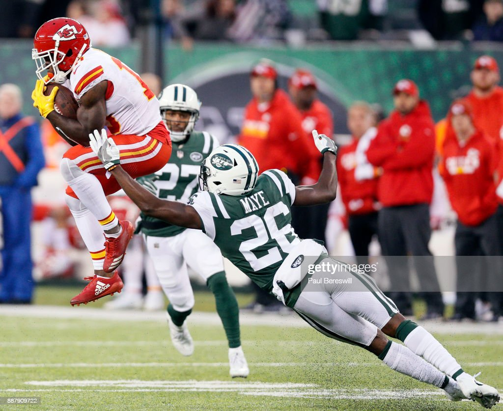 Tyreek Hill #10 of the Kansas City Chiefs pulls in a pass for a 40 yard gain with about two minutes left in the fourth quarter as he caught it under coverage of Darryl Roberts #27 and Marcus Maye #26 of the New York Jets in an NFL football game on December 3, 2017 at MetLife Stadium in East Rutherford, New Jersey. Jets won 38-31.