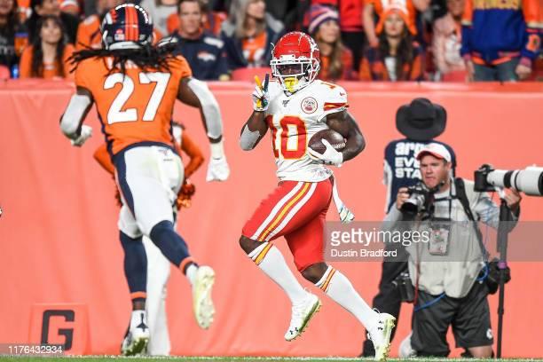 Tyreek Hill of the Kansas City Chiefs runs enroute to scoring a third-quarter touchdown against the Denver Broncos as Davontae Harris of the Denver...