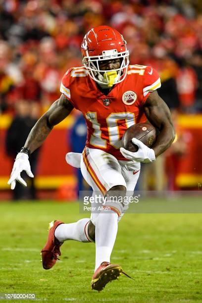 Tyreek Hill of the Kansas City Chiefs rushes the ball against the Oakland Raiders during the second half of the game at Arrowhead Stadium on December...