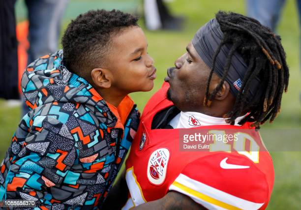 Tyreek Hill of the Kansas City Chiefs teases his son Zev by leaning away from a kiss during pregame warmups prior to the game against the Oakland...