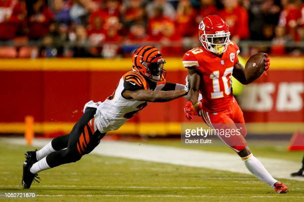 Tyreek Hill of the Kansas City Chiefs tries to avoid being pushed out of bounds by Tony McRae of the Cincinnati Bengals during the second quarter of...