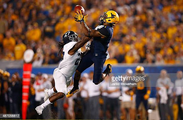 Tyrek Cole of the West Virginia Mountaineers catches a pass in front of Deshawntee Gallon of the Georgia Southern Eagles during the game at...