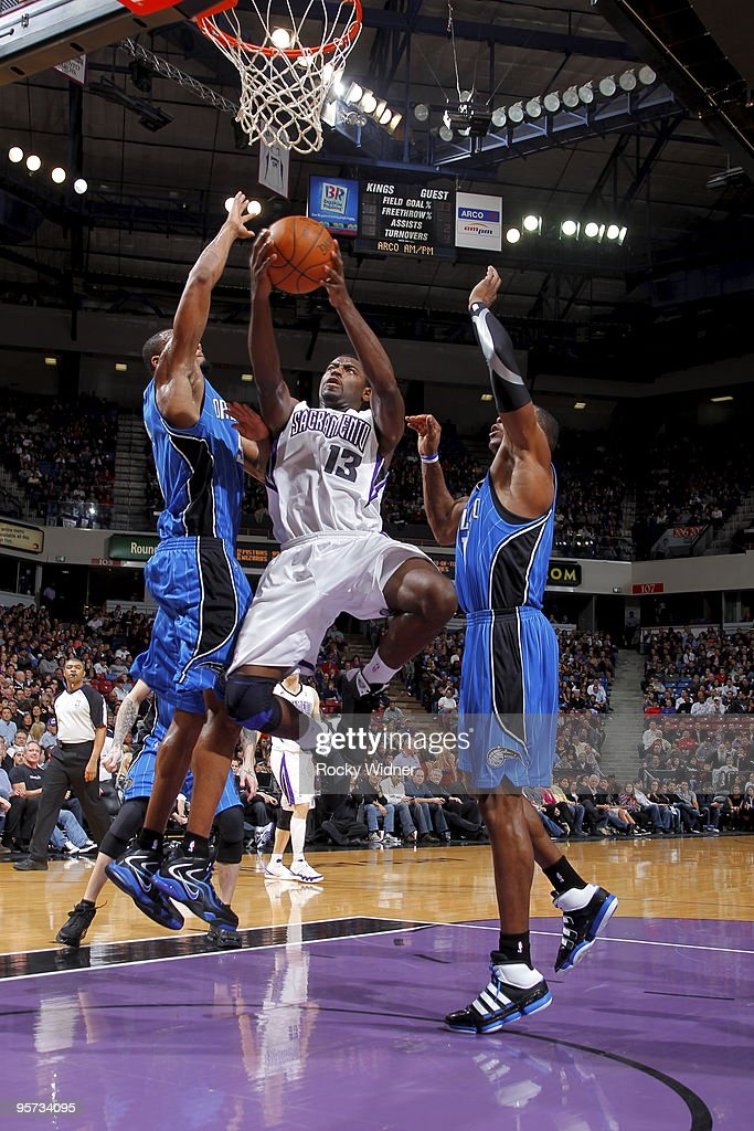 Tyreke Evans #13 of the Sacramento Kings gets to the basket against Rashard Lewis #9 and Dwight Howard #12 of the Orlando Magic on January 12, 2010 at ARCO Arena in Sacramento, California.