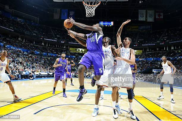 Tyreke Evans of the Sacramento Kings goes to the basket against Serge Ibaka and Thabo Sefolosha of the Oklahoma City Thunder during the game at the...