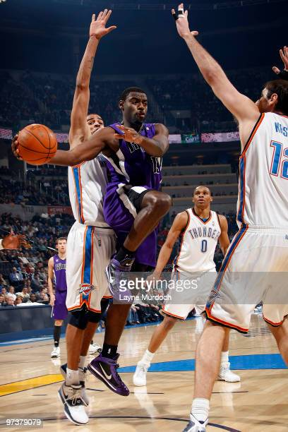Tyreke Evans of the Sacramento Kings passes the ball around Nenad Krstic of the Oklahoma City Thunder on March 2 2010 at the Ford Center in Oklahoma...