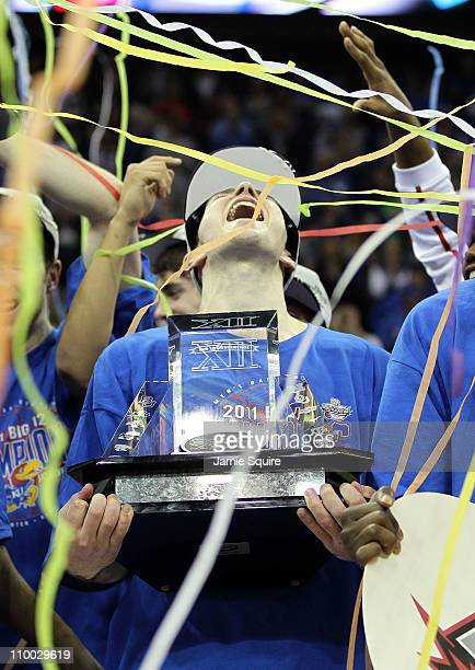 Tyrel Reed of the Kansas Jayhawks celebrates with the Big 12 championship trophy after defeating the Texas Longhorns 8573 in the 2011 Phillips 66 Big...