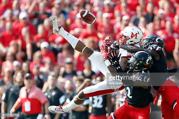 Tyrell Gilbert of the Cincinnati Bearcats and Alex Thomas of the Cincinnati Bearcats break up a pass intended for James Gardner of the Miami Ohio...