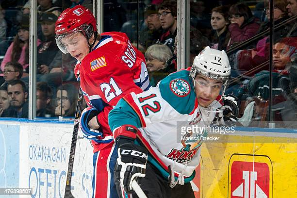 Tyrell Goulbourne of the Kelowna Rockets checks Matt Sozanski of the Spokane Chiefs during the first period on March 5, 2014 at Prospera Place in...