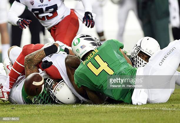 Tyrell Johnson of the Arizona Wildcats loses the ball against the defense of Erick Dargan of the Oregon Ducks in the first half of the PAC12...
