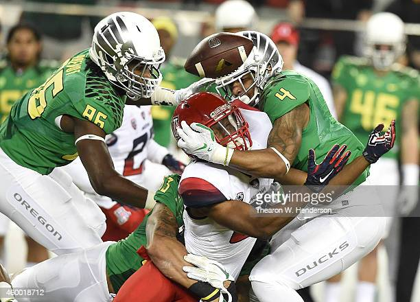 Tyrell Johnson of the Arizona Wildcats loses the ball against the defense of Erick Dargan of the Oregon Ducks and Torrodney Prevot of the Oregon...