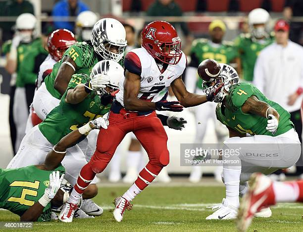 Tyrell Johnson of the Arizona Wildcats loses the ball against the defense of Erick Dargan of the Oregon Ducks and Tyson Coleman of the Oregon Ducks...