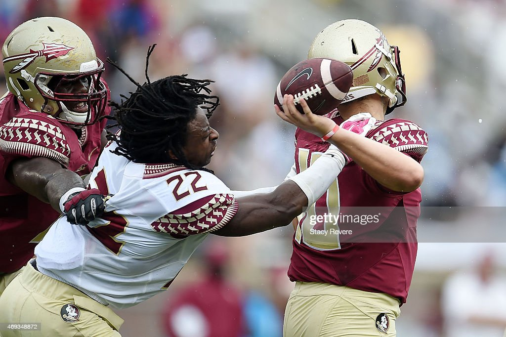 Tyrell Lyons #22 of the Gold team pressures Sean Maguire #10 of the Garnet team during Florida State's Garnet and Gold spring game at Doak Campbell Stadium on April 11, 2015 in Tallahassee, Florida.