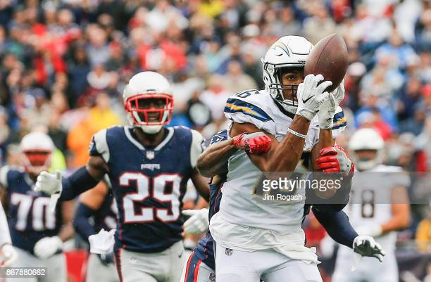 Tyrell Williams of the Los Angeles Chargers catches a pass as he is defended by Jonathan Jones of the New England Patriots during the third quarter...