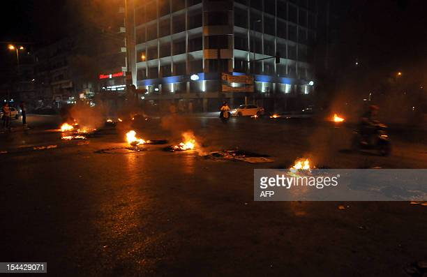Tyres burn after being set on fire by Lebanese protesters in the northern city of Tripoli on October 19 2012 to protest against the assassination of...