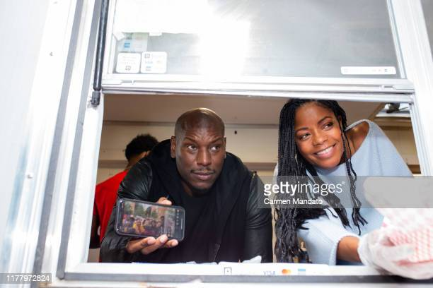 Tyrese Gibson and Naomie Harris are seen serving from a food truck during the Black Blue cast members' visit to Morehouse College on October 24 2019...