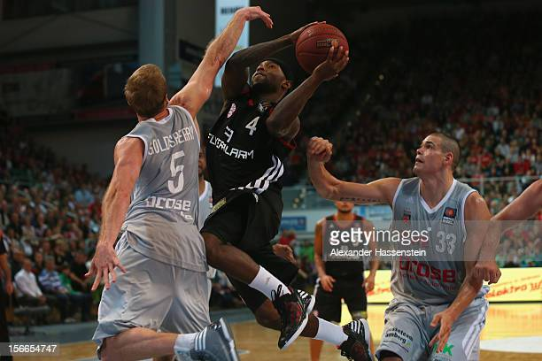 Tyrese Rice of Muenchen shoots against John Goldsberry of Bamberg and his team mate Maik Zirbes during the Beko Basketball match between Brose...