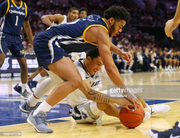 Tyrese Williams of the Quinnipiac Bobcats and Jahvon Quinerly of the Villanova Wildcats fight for control of a loose ball during the second half of a...